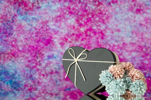 Caja de corazón de vista frontal con flores de colores de tapa negra sobre fondo rosa borroso con espacio libre