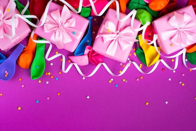 Caja decorativa regalos composición bolas inflables serpentina fondo púrpura