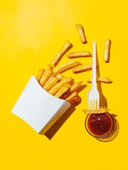 Caja derramada de papas fritas con salsa de tomate y tenedor