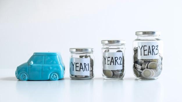 Caja de dinero del coche y botella de vidrio con monedas dentro.