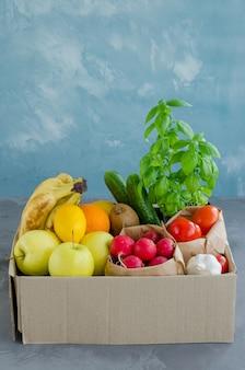 Caja de donación con frutas orgánicas frescas, verduras y hierbas. entrega de alimentos saludables al hogar.