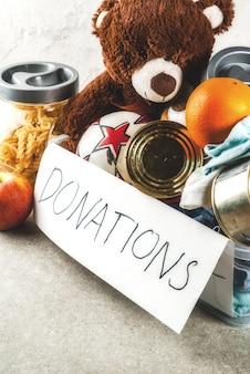 Caja de donación de plástico con juguetes, ropa y comida sobre fondo gris blanco