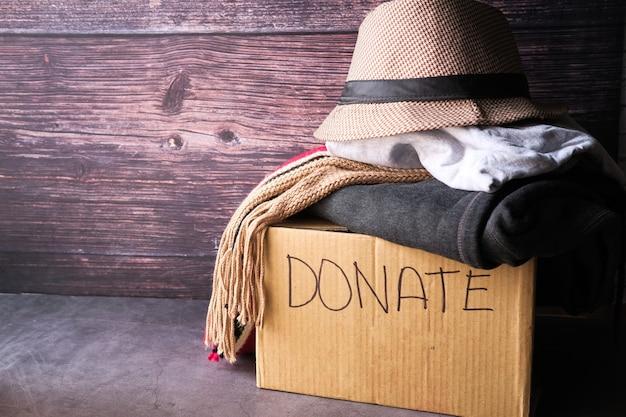 Caja de donación con ropa de donación en una mesa de madera.