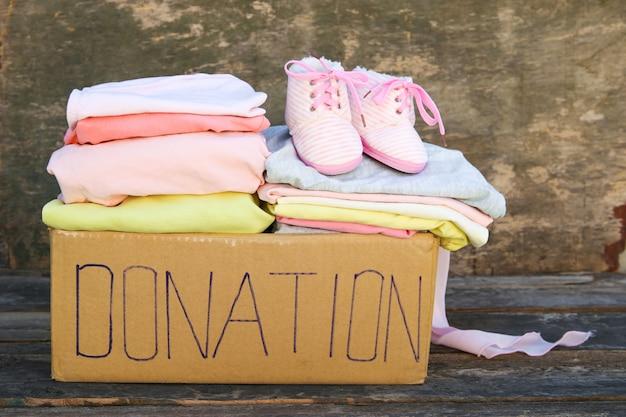Caja de donación con ropa en la madera vieja