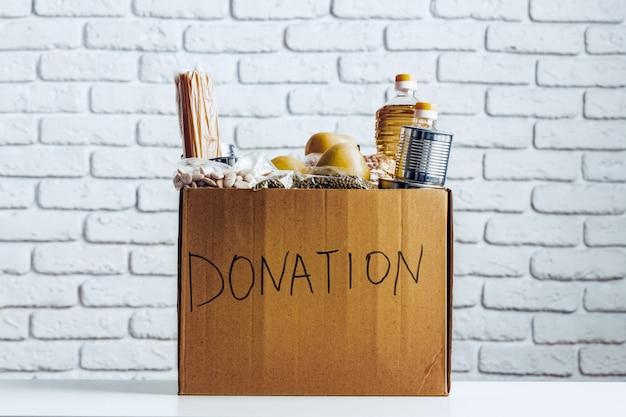 Caja de donaciones con comida enlatada sobre la mesa