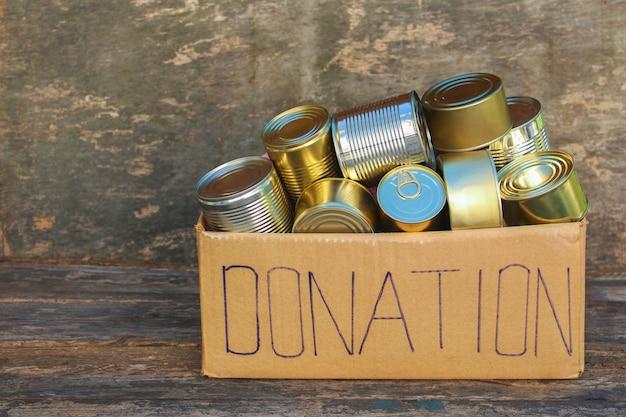 Caja de donaciones con diferentes alimentos enlatados.