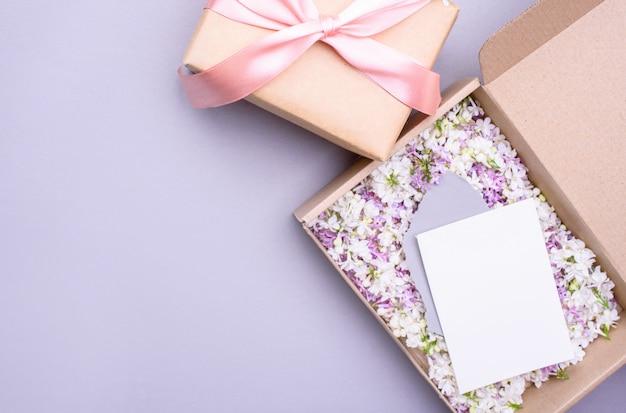 La caja ecológica está llena de flores lilas de diferentes colores y una postal blanca de felicitación.