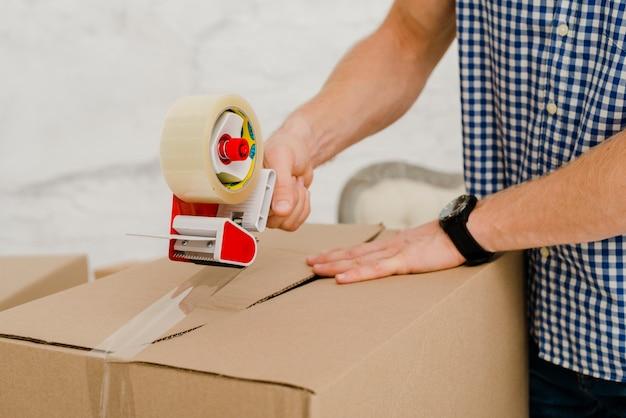 Caja de embalaje del hombre de cultivo con cinta adhesiva