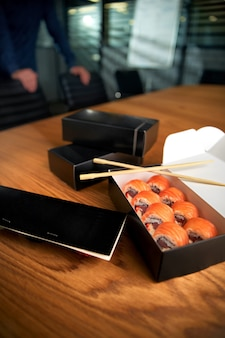 Caja de entrega de rollos de sushi en el espacio de trabajo con palillos. almuerzo de oficina