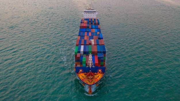 Caja del envase del buque de la carga del cargo que lleva para la importación y exportación logística y transporte del negocio por el buque de carga en el mar abierto, vista aérea.
