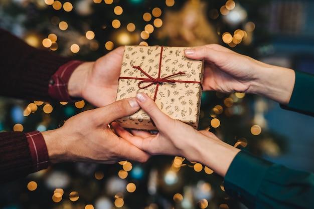 Caja envuelta en manos de mujer y hombre. esposo cariñoso felicita a su esposa con año nuevo
