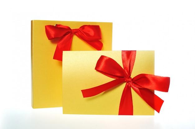 Caja festiva de oro con un lazo rojo.