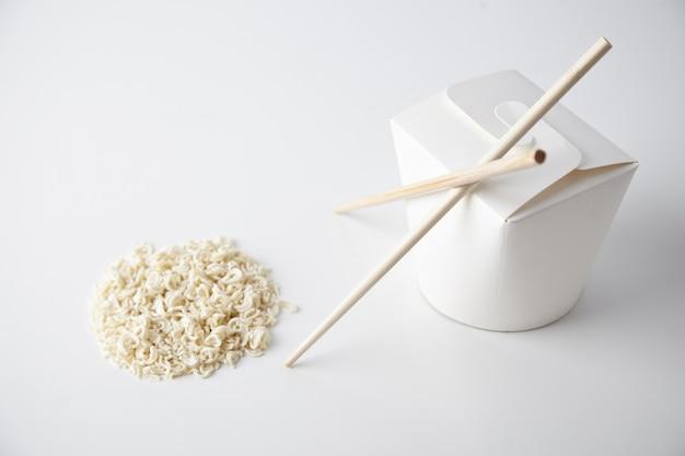 Caja de fideos para llevar en blanco cerrada con palillos cerca de pasta seca en forma de círculo aislado en blanco presentación comercial de enfoque cercano