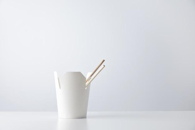 Caja de fideos para llevar en blanco con palillos en el interior presentado en el lateral y aislado en blanco