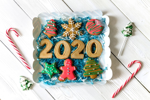 Caja con figuras de pan de jengibre 2020 y otros dulces navideños tradicionales. bastón de caramelo, copo de nieve redondo y hombre de jengibre, piruleta estrella. vista superior. endecha plana. concepto de navidad