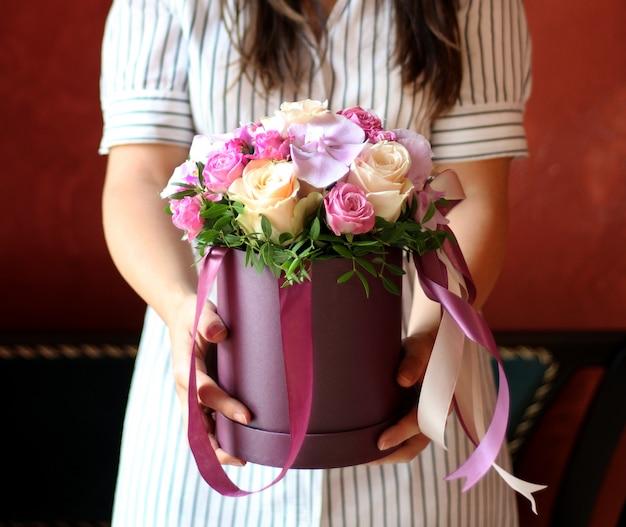 Caja de flores con lazo en manos de niña.