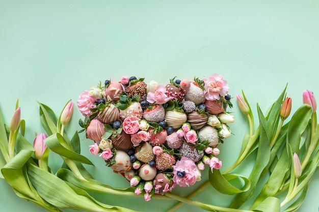 Caja en forma de corazón con fresas cubiertas de chocolate hechas a mano con diferentes ingredientes y flores como regalo en el día de san valentín en fondo rosa con espacio libre para texto
