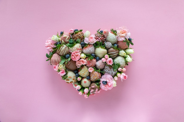 Caja en forma de corazón con fresas cubiertas de chocolate hechas a mano con diferentes ingredientes y flores como regalo en el día de san valentín sobre fondo rosa
