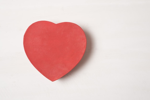Caja en forma de corazón rojo aislar sobre superficie blanca