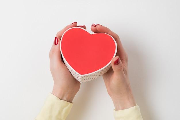 Caja en forma de corazón rojo de estilo vintage en mano femenina aislado en