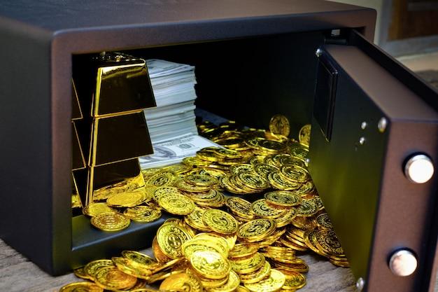 Caja fuerte de acero llena de monedas y lingotes de oro.
