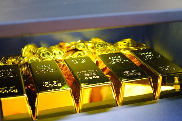 Caja fuerte de acero llena de monedas y pila de lingotes de oro