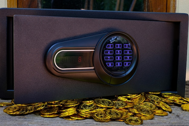 Caja fuerte de acero llena de pila de monedas y barra de oro en la mesa de madera