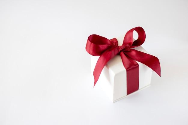 Caja gif blanca con un lazo rojo sobre un fondo blanco.