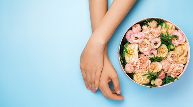 Caja con hermosas flores junto a las manos de la mujer sobre el fondo azul con espacio de copia. belleza
