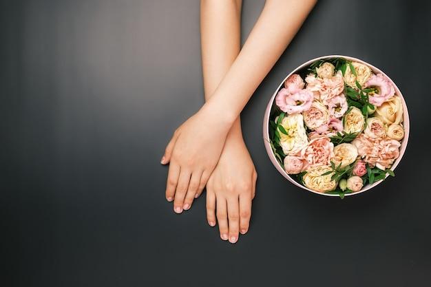 Caja con hermosas flores junto a las manos de la mujer sobre el fondo negro con espacio de copia. belleza