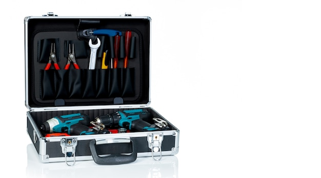 Caja de herramientas aislada sobre fondo blanco. caja de herramientas negra con herramientas. alicates, llave inglesa o llave inglesa, destornillador, cortador y taladro destornillador inalámbrico en caja de herramientas.