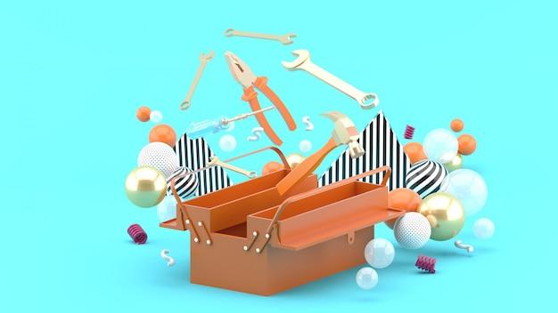 Caja de herramientas en medio de bolas de colores en azul. representación 3d