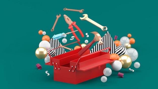 Caja de herramientas en medio de bolas de colores en verde. representación 3d
