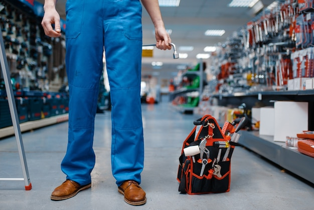 Caja de herramientas en tienda de herramientas, trabajador masculino en uniforme. elección de equipos profesionales en ferretería, supermercado de instrumentos