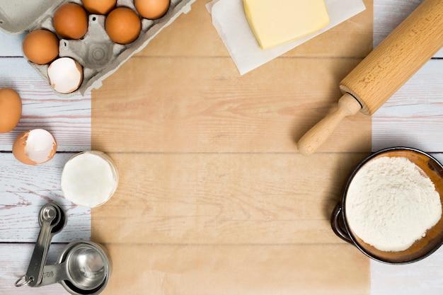 Caja de huevos; mantequilla; rodillo; harina y cuchara medidora sobre mesa de madera.