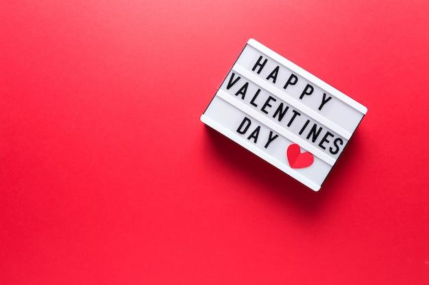 Caja con la inscripción feliz día de san valentín en un fondo rojo.