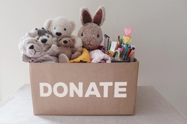 Una caja llena de juguetes usados, paños, libros y artículos de papelería para donación.
