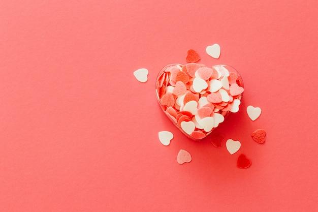 Caja llena de muchos pequeños corazones de coral vivos. composición para una tarjeta con un lugar para texto.