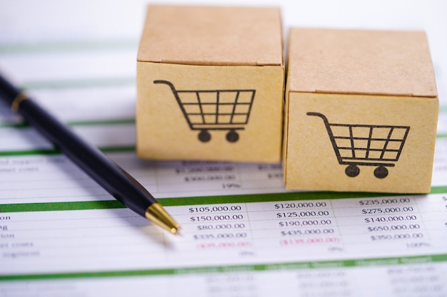 Caja con logotipo de carrito de compras en papel de hoja de cálculo con bolígrafo.