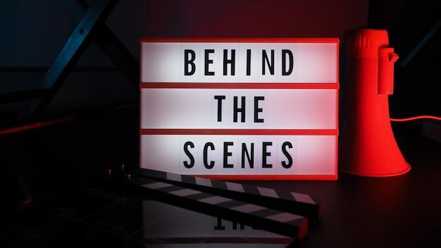 Caja de luz detrás de escena. texto en caja de luz de cine. megáfono y silla de director y pizarra de película al lado. detrás del concepto de escena.