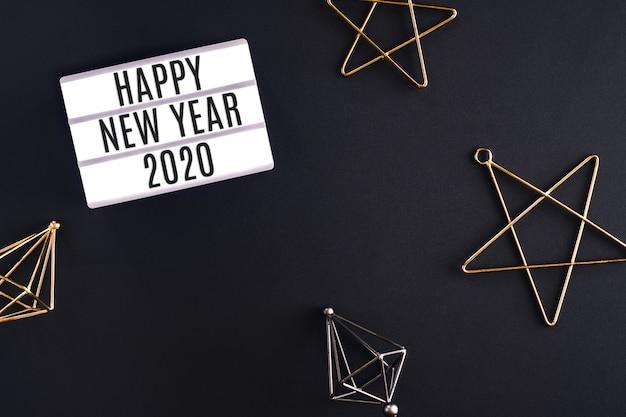 Caja de luz de fiesta de feliz año nuevo 2020 con vista superior de elemento de decoración de estrella sobre mesa de fondo negro