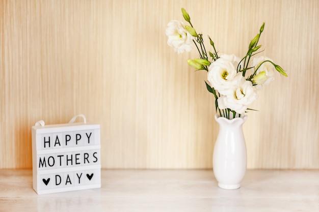 Caja de luz con letras feliz día de la madre, flores blancas eustoma o lisianthus en jarrón sobre mesa de madera con espacio de copia.