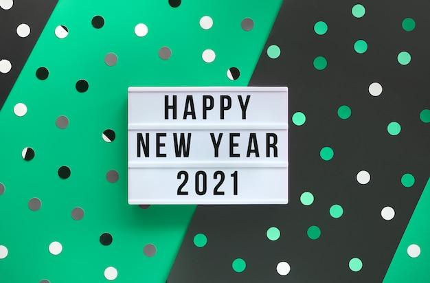 Caja de luz con texto feliz año nuevo 2021. capas de papel verde y negro con confeti, lunares.