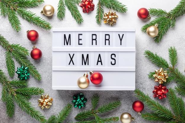 Caja de luz con texto feliz navidad, bolas de navidad doradas y rojas y rama de abeto sobre fondo de piedra