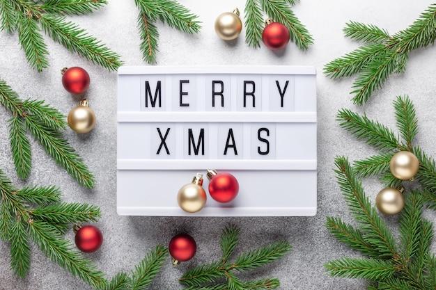 Caja de luz con texto feliz navidad, bolas navideñas doradas y rojas y rama de abeto
