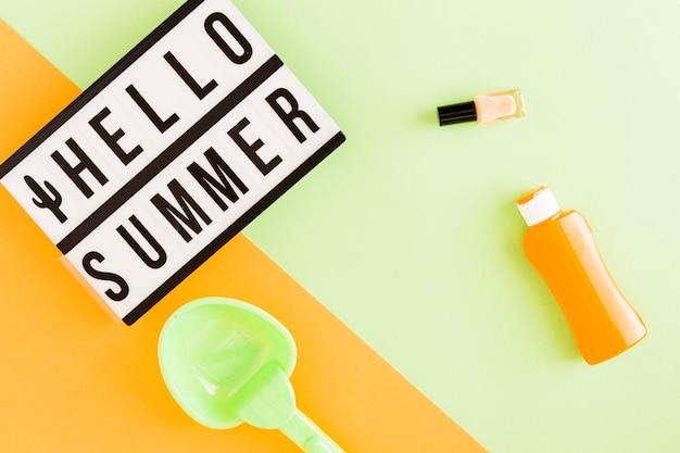 Caja de luz con texto hello summer y artículos de vacaciones.