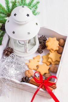 Caja de madera blanca con galletas caseras y decoraciones navideñas.