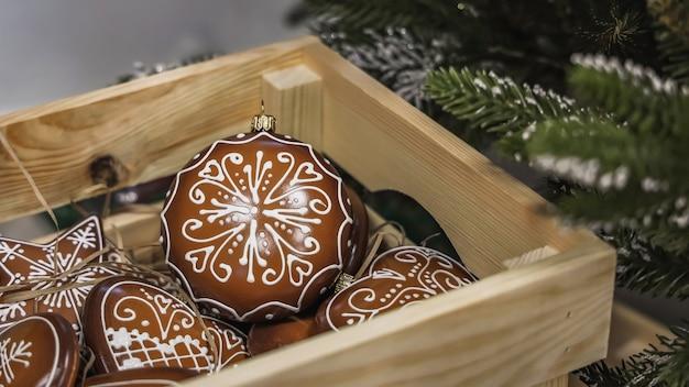 Caja de madera con bolas decorativas navideñas hechas a mano y juguetes en las ramas de pino verde