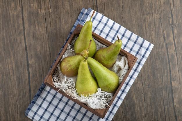 Caja de madera de deliciosas peras maduras sobre fondo de madera