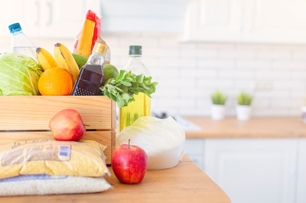 Una caja de madera de diferentes alimentos, frutas, verduras, aceite, agua, azúcar en la cocina. entrega a domicilio segura. copyspace